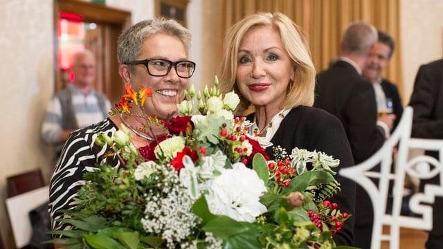 Zwei Frauen lachen in die Kamera, mit einem Blumenstrauss. LInks BErnadette Gächter.