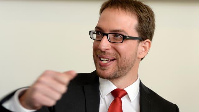 Ein Mann mit dunkler Brille, lachend.