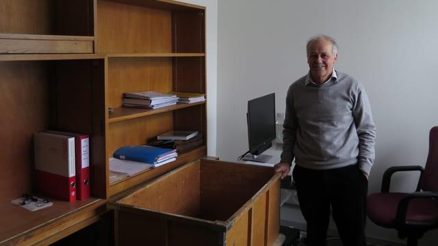 Aldo Quadri neben fast leerem Büchergestell aus Holz.