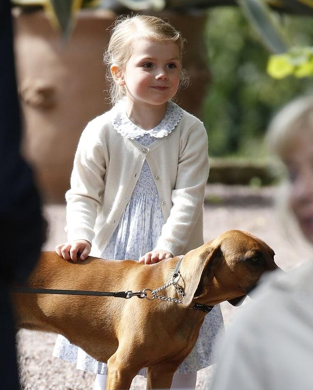 Ein Mädchen im blauen Kleid streichelt einen Hund.