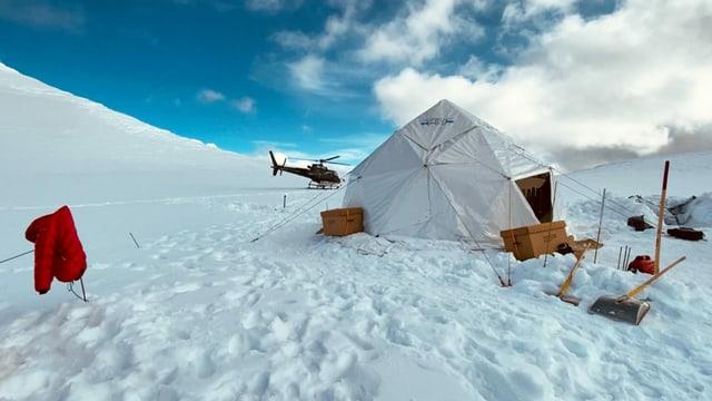 Zelt auf einer Eisfläche. Im Hintergrund ein Helikopter.