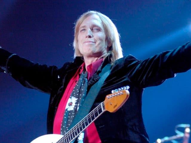 Tom Petty im schwarzen Anzug breitet die Arme aus. Er steht auf einer Bühne und hat sich eine Gitarre um den Hals gehängt.