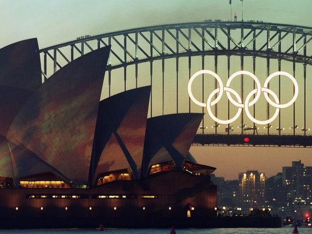 Fünf beleuchtete Ringe an der Harbour Brigde mit dem Opernhaus im Vordergrund.