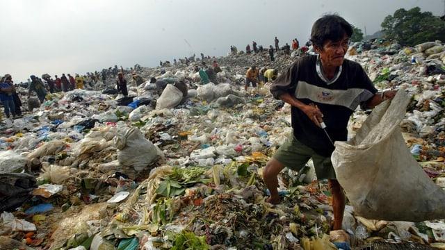 Ein Mann sammelt wiederverwertbaren Abfall und Nahrungsmittel für die Familie