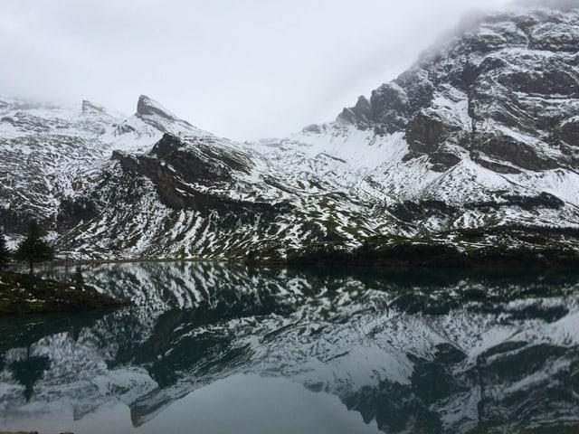 Wolkenverhangene Berglandschaft mit Schnee