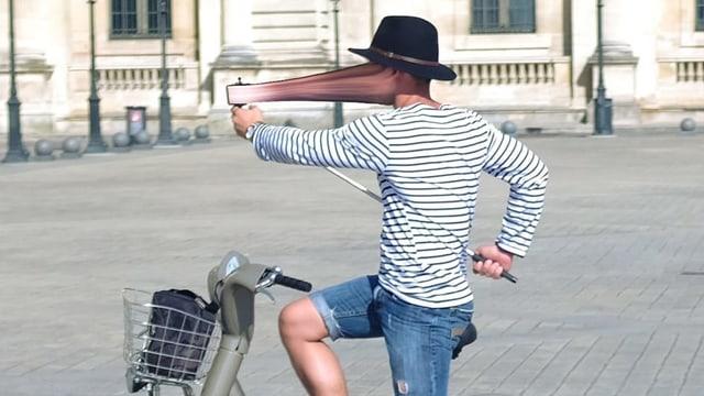Ein junger Mann sitzt auf einem Fahrrad und nimmt mit einem Smartphone ein Bild von sich auf.