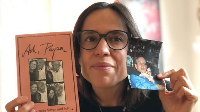 Annette König hält das Buch «Ach, Papa» von Mareike Nieberding in der Hand und dazu noch ein Foto ihres Vaters