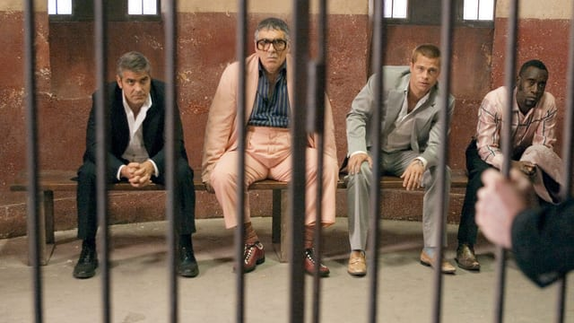 Vier Männer sitzen hinter Gitterstäben auf einer Bank.
