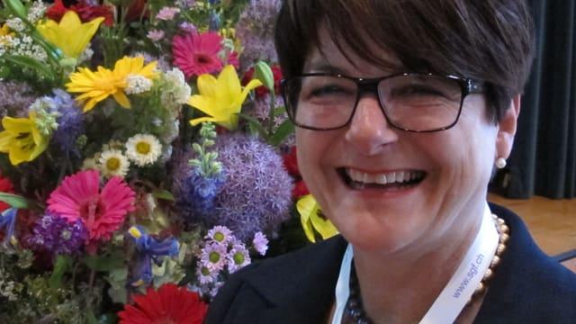 Priska Stalder lächlt in die Kamera. Sie trägt eine Brille mit schwarzen Rändern und einen dunklen Blazer, im Hintergrund sieht man einen riesigen Blumenstrauss.