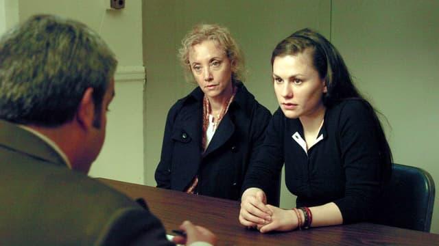 Eine ältere Frau und eine junge Frau sitzen einem Mann gegenüber.