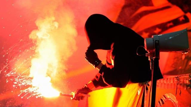 Ein Hooligan zündet eine rot leuchtende Petarde, sein Gesicht ist vermummt.