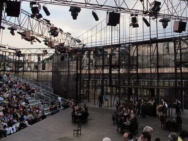 Blick in die Verdi-Arena, ein Gerüst aus Stahl, Schauspieler auf der Bühne, Publikum im Zuschauerraum.
