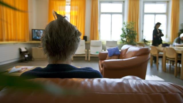 Eine Frau von hinten sitzt auf einem Sofa.