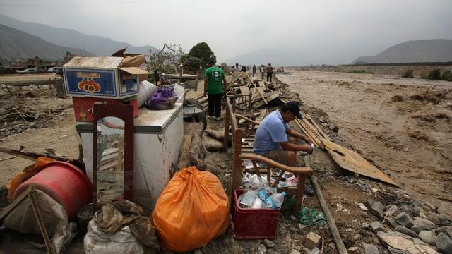 Ein Mann sitze an einem Fluss, daneben einige Habseligkeiten, die er retten konnte.