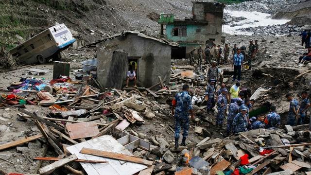 Verschüttetes Dorf, Rettungskräfte, einzelne Häuser, viel Schutt und Müll