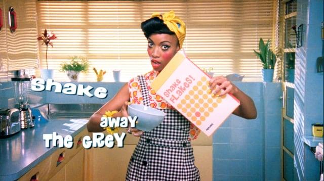 Eine Frau in Hausfrauen-Kleidung schüttet Cornflakes in eine Schüssel.