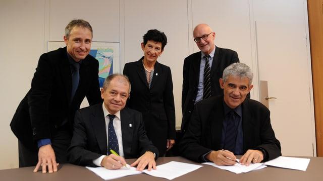 Fünf Personen beim Unterzeichnen der Vereinbarung