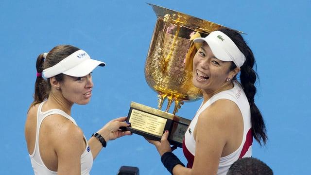 Martina Hingis und Yung-Jan Chan halten die Trophäe in die Höhe.