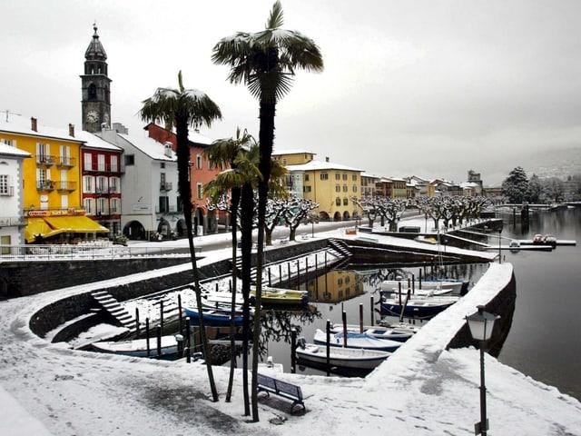Die Uferpromenade in Ascona mit dem kleinen Hafen und den Palmen sind mit Schnee bedeckt.