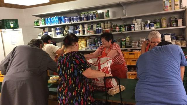 Menschen in Pirmasens besorgen sich Lebensmittel an einer Theke.