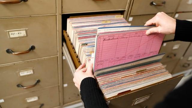 Zwei Hände ziehen eine Akte aus einem geöffneten Archivschrank des Stadtarchivs Bern heraus.