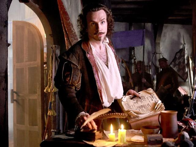 Rafe Spall als William Shakespeare steht vor einem Schreibtisch.