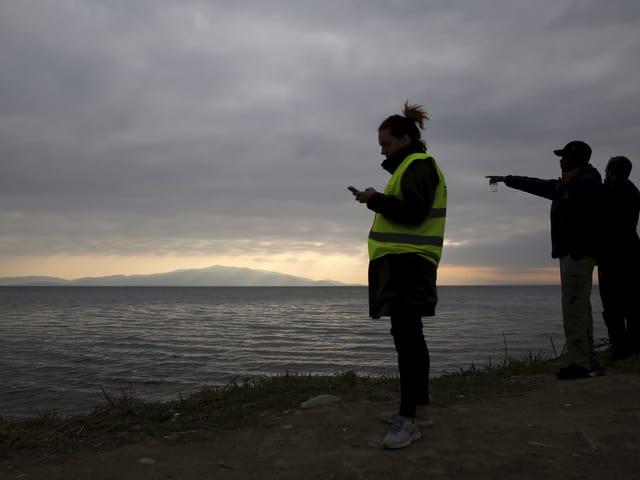 Drei Personen stehen am Strand, eine zeigt aufs Meer hinaus, eine andere – sie trägt eine gelbe Signalweste – schaut auf ihr Handy, das sie in der Hand hält.