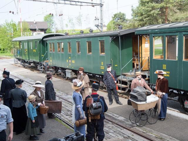 Statisten vor Dampfbahn am Bahnhof