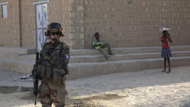 Ein Soldat in voller Kampfmontur mit gesenktem Maschinengewehr im Vordergrund. Dahinter zwei Kinder vor einer Hausmauer.
