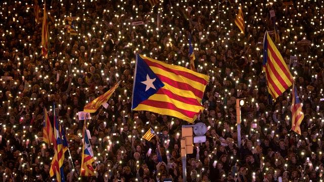 Demonstranten mit katalanischer Flagge und Kerzenlichtern.