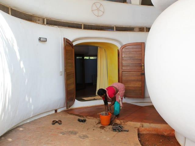 Frau putzt Boden vor einer Haustür.