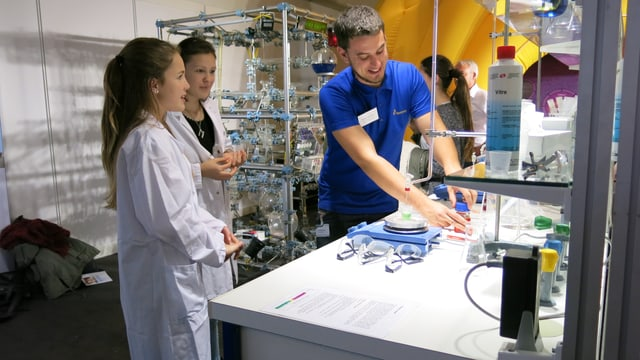 Mann erklärt zwei jungen Frauen am Labortisch