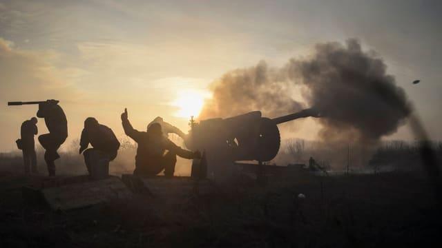 Symbolbild: Ukrainische Soldaten feuern im Gegenlicht eine Kanone ab.