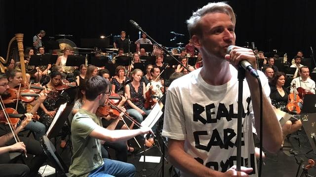 Ein Orchester, davor ein Mann am Mikrofon.