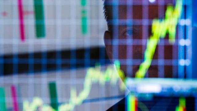 Hinter einem Aktienindex spiegelt sich das Gesicht eines Mannes.