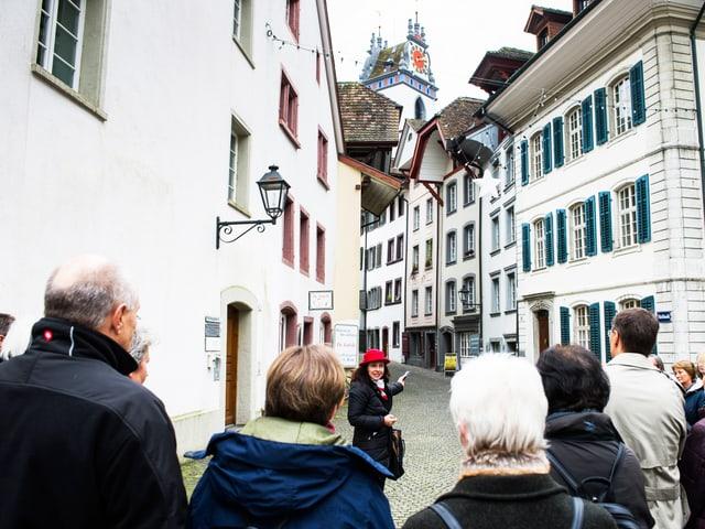 Eine Gruppe von Menschen in der Altstadt von Aarau. Hinten sind einige Gebäude.