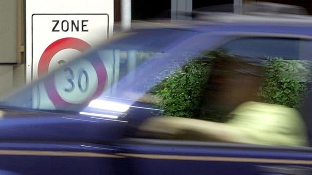 Auto fährt vor Tempo 30 Schild vorbei