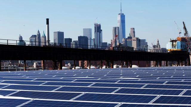 Symbolbild: Fotovoltaikanlage im Vordergrund, im Hintergrund die Skyline von New York City.