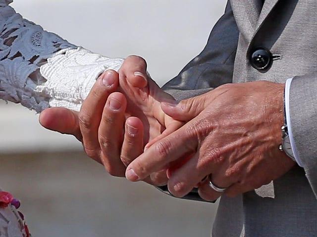 Die Hände von George Clooney und Amal Alamuddin in Nahaufnahme