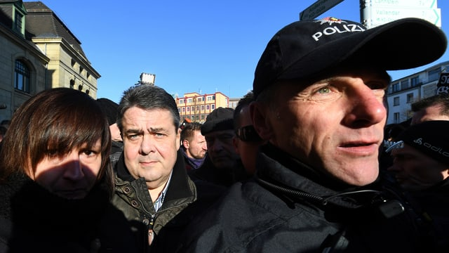 Policists en unifurma protegian a Sigmar Gabriel.