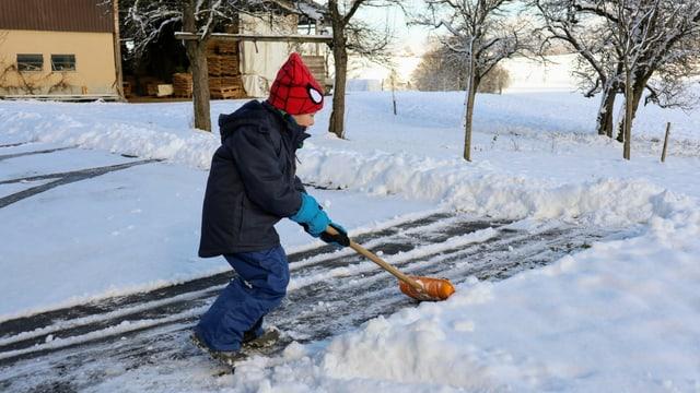 Kind am Schneeschaufeln