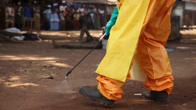 Ein Mitglied des Roten Kreuzes disinfiziert den Boden im Dorf Forecariah in Guinea