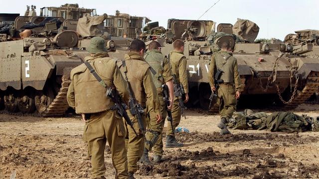 Israelische Soldaten marschieren auf abgestellt Panzer zu