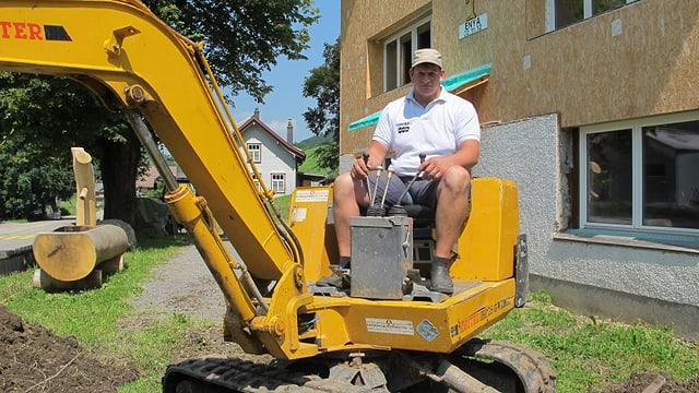 Urs Abderhalden sitzt auf einem Gartenbagger vor seinem Haus, das er derzeit umbaut.