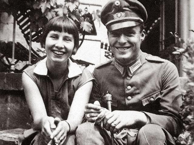 Historisches Foto: Eine junge Frau und ein junger Mann posieren lachend nebeneinander. Er trägt eine Soldatenuniform.