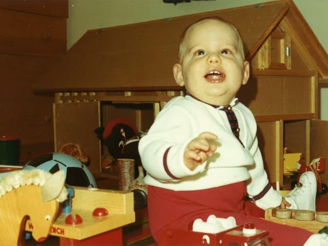 Baby-Junge sitzt erfreut vor Spielzeug-Stall.