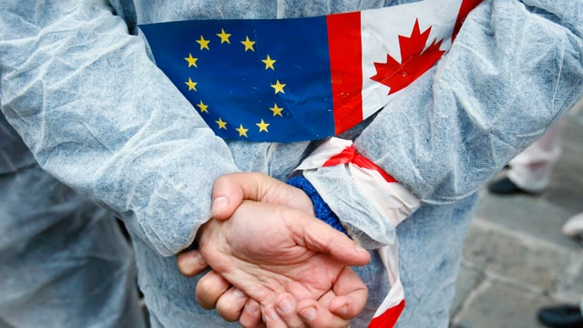 Eine Person verschränkt die Arme auf dem Rücken. Auf dem Rücken trägt die Person die kanadische Flagge und jene der EU.