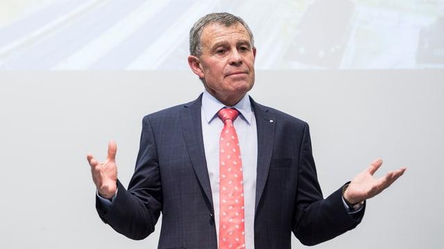 Ein Mann mit Anzug und roter Krawatte, die Hände ausgestreckt