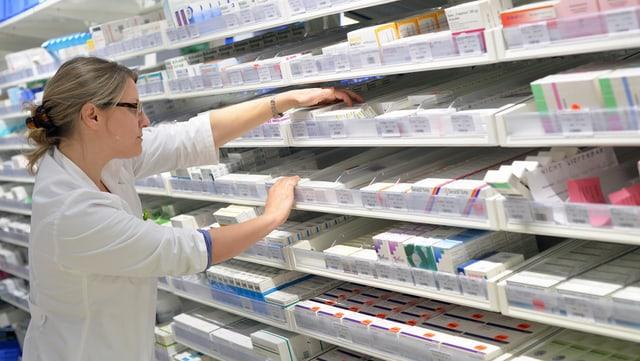 Eine Angestellte in einer Apotheke nimmt Medikamente aus dem Gestell.