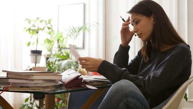 Frau schaut Rechnungen an